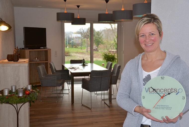 Eine Frau steht im Wohnzimmer und lächelt in die Kamera. Sie hält eine Uhr in der Hand