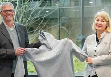 Zwei Erwachsene lächeln in die Kamera und halten einen Pullover in den Händen