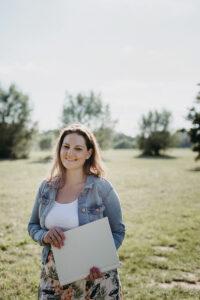 Eine Frau steht auf einer Wiese und lächelt in die Kamera